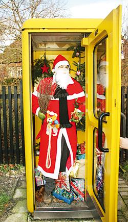 Weihnachtsmann in Telefonzelle