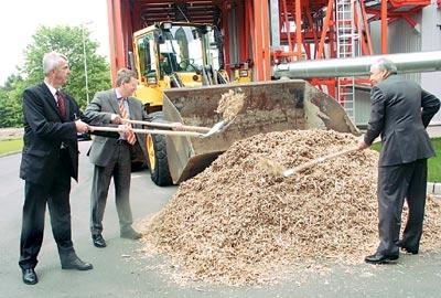 E.ON-Geschäftsführer Bernd Romeike, Ministerpräsident Christian Wulff und Michael Feist, Vorstandsvorsitzender der Stadtwerke Hannover, schaufeln Holzhackschnitzel in die Schaufel des Radladers. Im Biomassekraftwerk wird dieser Vorgang maschinell abgewick