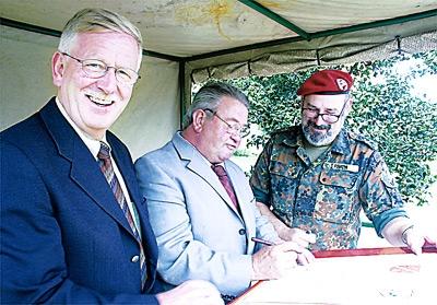 Bürgermeister Walter Hotze unterzeichnet die Patenschaftsurkunde. Links: Gemeindedirektor Wilfried Henking, rechts: Hauptmann Torsten Paick. Fotos: Hildebrandt