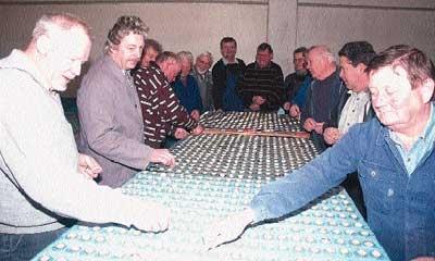 Mitglieder des Männergesangvereins Landesbergen kleben Kronkoren auf Kunststoffplatten, die nächsten Juni zur 950-Jahrfeier des Dorfes das Fußballfeld des Sportplatzes abdecken sollen. 2,5 Millionen Kronkorken werden benötigt. Ein Rekordversuch. Foto: Hil