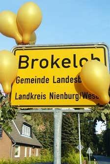 Brokeloh, das Golddorf: Goldene Luftballons am Ortsschild machen es deutlich