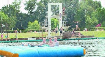 Junge Leute aalen sich auf der Riesenluftmatratze auf dem Weseraltarm. Dahinter hüpfen Badegäste vom Sprungturm.Foto: Reckleben
