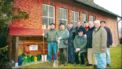 Diese Rentner bauten auf dem Friedhof in Schessinghausen Gerätehäuschen (links) und eine Toilette. Darüber freut sich auch Bürgermeister Friedel Fischer (4. von links).