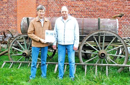Heimatvereins-Vorsitzender Chris Weug und -Mitglied Gerhard Harmening (rechts) stellten den historischen Kalender vor dem Domizil des Heimatvereins vor.