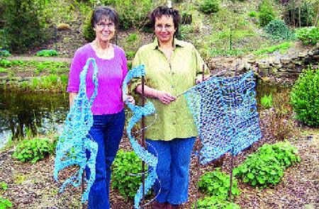 Die Dozentinnen Marie-Luise Prinzhorn und Adina Sternemann beim Dekorieren der geklöppelten Gartenkunst, die Teil der Ausstellung ist